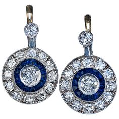 Art Deco Sapphire Diamond Gold Earrings. The center round diamond is surrounded by a ring of calibré cut sapphires and a halo of of round cut smaller diamonds.