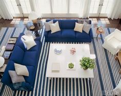 Sailor's Haven ~ Nautical colors inspired the living room of a Hamptons home decorated by Victoria Hagan. The blue and white linens on the sofas and chairs are from Clarence House and Henry Calvin Fabrics, respectively; the white-lacquer cocktail table is a Hagan design; and an oversize antique dhurrie from the Rug Loft covers the floor.