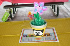 Yo Gabba Gabba Centerpiece (Plex).  Yo Gabba Gabba characters made with terra cota pots, acrylic paint, painted Yo Gabba Gabba characters by hand, used square foam and cut to fit inside the pots, added Easter grass, and stuck the fake flowers and mini pinwheels into the foam.