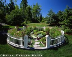 This circular flower garden with its bird-house fence posts is wonderful.