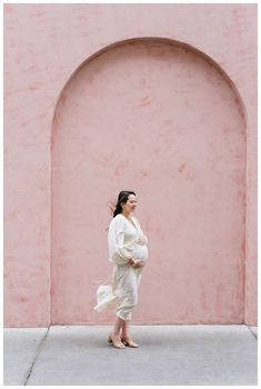 Pregnant woman in front of pink wall at Olde Pink House in Savannah. Downtown Savannah Georgia family photos photographed by Kristen M. Brown of Samba to the Sea Photography. #savannah #savannahga #familyphotos