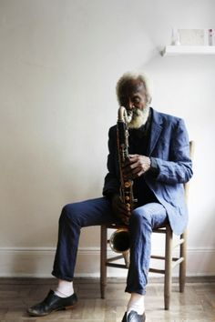 An old looking guy in a simple envirnment, playing some funky jazz