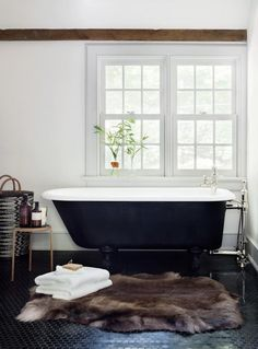 In the master bathroom of a Bedford, New York, former farmhouse, architect Rafe Churchill had an existing bathtub painted black and the floor finished in black granite mosaic tile.