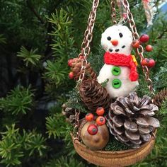 Primitive snowman with berries and cones hanging ornament in rusty lid.