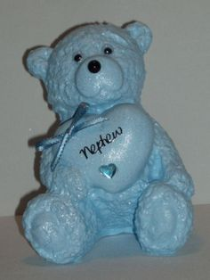 This beautiful teddy bear grave memorial is painted in baby blue, a little added glitter to make it sparkle, googly eyes and little black nose give it the cute factor.  With this baby blue teddy bear grave memorial holding a heart upon which the word Nephew will be in shining silver lettering. Finished off with a blue ribbon bow (ribbon designs may vary) and a plastic blue gem heart.