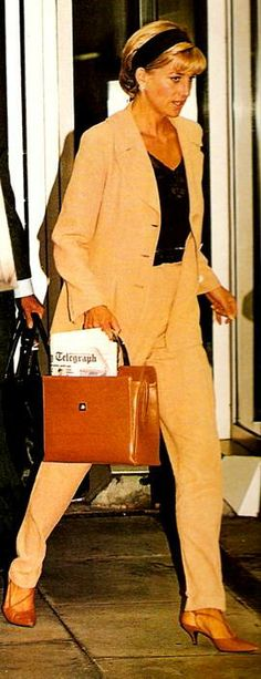 Princess Diana, wearing sand coloured suit with black top & matching headband with tan shoes & bag.