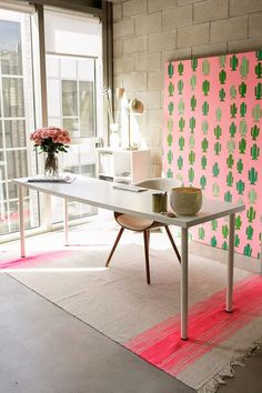LOVELY LITTLE CORNERS -  Workspaces - CREATE & CULTIVATE'S OFFICE -   Severe looking concrete spaces can become whimsical with the right touches of color and glam.  In this case, pink rules, with the pink fabric  dottend with various perky colors of green cactus, stretched over a large square frame.  a simple pink boquet of roses  and quirky vase of  feathered arrows, keeps things from being overly toy like.  ~TAB
