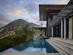 Designed by Olson Kundig Architects, a majestic villa comprised of concrete, glass, stone and steel is perched atop a hillside in Shek-O, Hong Kong Island.