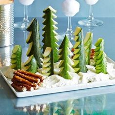Snowy Scene Use our fresh local cucumbers to make this snack that doubles as adorable holiday decor. Compliments come standard when you make even the simplest snack interactive and fun! Ingredients: 1 cucumber,  1 zucchini, Ranch dip, Pretzel sticks Directions:Quarter or halve a cucumber and a zucchini lengthwise. Using a paring knife, trim each piece to create a pointed tip. Cut out wedges to form branches. Spoon ranch dip on a plate. Plant trees in dip; garnish with stacked pretzel