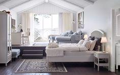 Chambre avec mur de miroirs lit garni de nombreux textiles