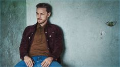 Front and center, James McAvoy wears a Tom Ford suede jacket, Gucci denim jeans, and a Prada knit polo.