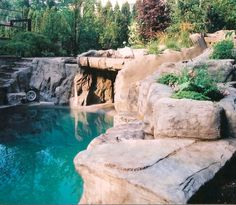 An artificial rock grotto, waterfall, stairs and slide into the custom pool!