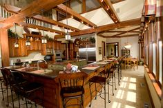 Two-story kitchen with a v-shaped bar for seating and hand-crafted rafters with built-in lighting above.