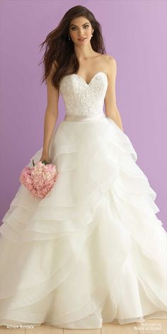 Designed to mimic rose petals, the ruffles of this strapless ballgown's full skirt unfold gracefully from the satin waistband.