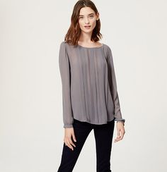 Pretty pleats dress up this beautifully sheer blouse. Add a cami beneath for more coverage. Jewel neck. Long raglan sleeves. Button cuffs. Hi-lo shirttail hem.