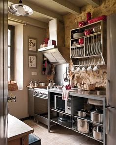 Petite mais fonctionnelle avec ses allures de cuisine professionnelle, cette cuisine allie le charme rustique d'un mur en pierre apparente et d'un vaisselier suspendu ancien avec des meubles et de l'électroménager en acier inox.