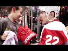 Canadian professional hockey player Jordin Tootoo makes a young fan's day during pregame warm-ups