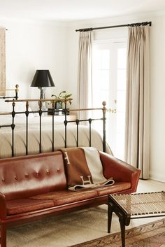 Black wrought iron bed, brown leather sofa, and neutral colors complete this bedroom.