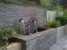 Stone veneer retaining wall by Huettl Landscape Architecture    If this were in our backyard, water would come out of it without a pump :P
