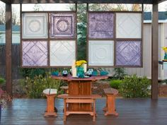 A table for a few is set to entertain in front of a tin tile privacy wall on the floating deck with shade structure.