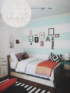 Break up your solid white room with bold stripes of light blue on an accent wall in your bedroom. Try a subtle color like Spring Blue by BEHR paint and pair it with black and white decor to achieve this eclectic look.