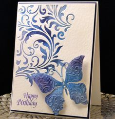 B-day card for Erin October 2016 Tim Holtz over a purple and blue Brusho's background. Penny Black Butterfly dry embossed with an EF. The solid back piece is really purple but looks navy in this photo. White hammered card stock for the front and base. Made by Peggy Dollar