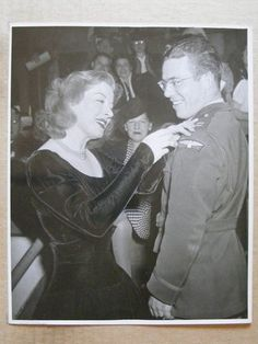 Greer Garson pins on award to soldier at a USO event during WWII.