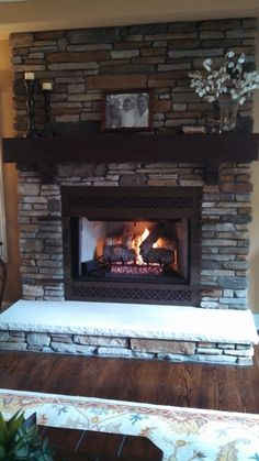 Aspen Southern by Boral Cultured Stone with wood mantel and limestone hearth