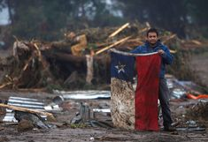 """""""A man holds up a Chilean flag in a flooded area after an earthquake in Pelluhue... about 200 miles, southwest of Santiago, Sunday, Feb. 28, 2010."""""""