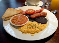 Enjoy a full English breakfast with black pudding, sausage, bacon, eggs, tomatoes, mushroom, and toast.