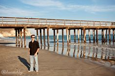 guy senior pictures on the beach in front of pier with sunglasses | Kiwi Ashby Photography