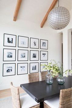 gallery wall of black and white family photos in black frames with thick white mats