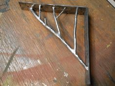 "hand forged metal ""corbels"", better known as ""shelf brackets"" with a branch motif. by steven brock 2015."