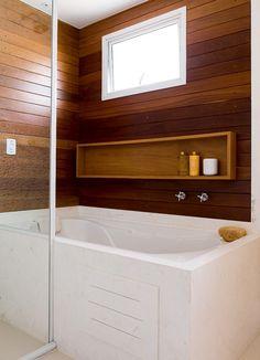 Tábuas de cumaru recobrem a área da banheira e dão ares de sala de banho a um dos banheiros da suíte do casal (Foto: Edu Castello/Editora Globo)