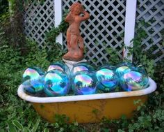 garden art using bathtub and globes, could use painted bowling balls too