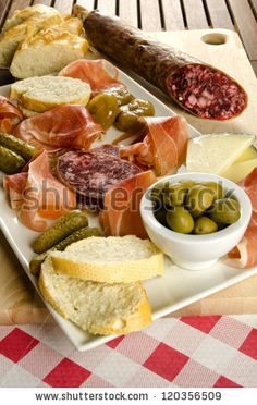 Homelike appetizer with salami, bread, olives, cheese, ham, pickles and red wine by MilaCroft, via Shutterstock