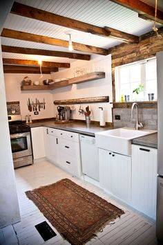 - white painted floors, rustic backsplash, open shelving.
