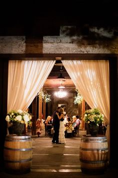 White curtains frame romantic views when pulled back against a barn doorway, especially when illuminated by the light inside.