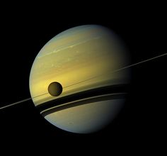 A giant of a moon appears before a giant of a planet undergoing seasonal changes in this natural color view of Titan and Saturn from NASA's Cassini spacecraft.    Titan, Saturn's largest moon, measures 3,200 miles, or 5,150 kilometers, across and is larger than the planet Mercury. Cassini scientists have been watching the moon's south pole since a vortex appeared in its atmosphere in 2012.