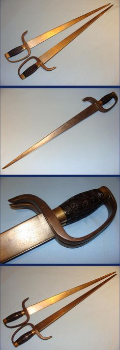 Chinese hudiedao fighting swords, 19th century, 63cms overall with broad pattern welded blades 12mm thick and 40mm wide at the base, they taper to a strong needle tip, being 2mm wide at this point. The hilt slabs are superbly carved in Rosewood with Chinese key pattern relief to the outer edges and floral carvings in the centre. Period repair to the tip of the right hand sword blade.