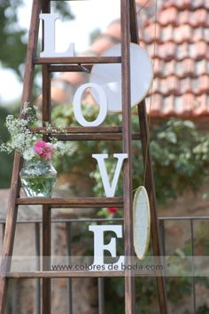 Vintage ladder with the word LOVE and vases with flowers Escalera vintage con la palabra LOVE y botes con flores