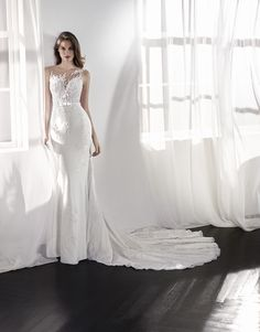 LANINA Romantic low waist mermaid wedding dress. An exquisite design with a two-piece effect that combines the sensuality of a fitted skirt, which stylizes the silhouette, and a bodice with an illusion neckline that plays with the sheer effects of the embroidered tulle and lace illusions, creating a very sexy second-skin effect. This sleeveless dress...  Citește mai mult »