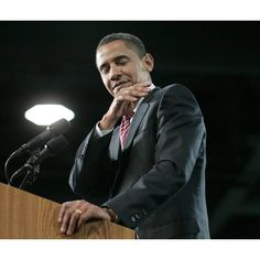 Democratic presidential hopeful, Sen. Barack Obama, D-Ill., jokingly dust off his shoulder as he speaks at a town hall-style meeting in Raleigh, N.C.,Thursday, April 17, 2008. (AP Photo/Jae C. Hong)