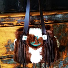 A custom hair on hide Bonnie Bag with the owners ranch brand in turquoise suede. . Made to order cowhide purses and totes from gowestdesigns.us.
