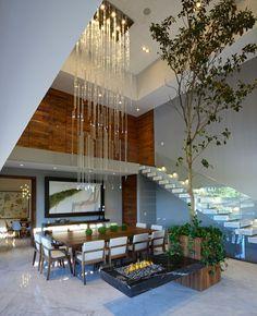 No interior da casa, com grande altura, chama atenção o lustre que se assemelha…