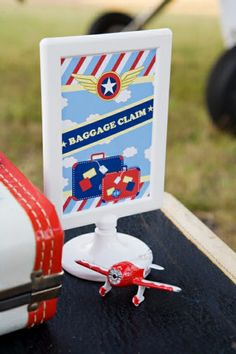 "Clever signage for the party favors that look like a ""baggage claim"" area at a Little Aviator Birthday Party"