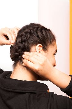 Santiago parted the hair down the middle and began braiding. For easier control and a flatter braid, she suggested folding each section under the one before it — not on top. Then, she twisted the bottoms of the braids over one another and set the hair with pins.