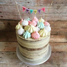 Nearly naked cake topped with pastel meringues and bunting