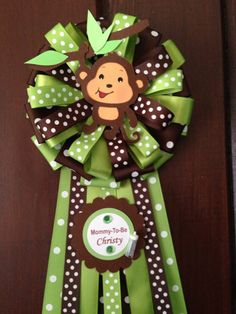 Mommy-To-be Baby Shower Monkey corsage for boy.  This Mommy To Be Corsage is great for the new mommy to wear at her baby shower!. These are corsages light and are designed to be pinned on a shirt. The Monkey is made with stock papar and have 3 layers. It includes a pin so that it can be secured to the shirt of the mom-to-be. This corsage will be shipped 2-4 days after payment is received.  Diameter of bow about 6.5 inches aprox. Total length of corsage is about 16 inches.