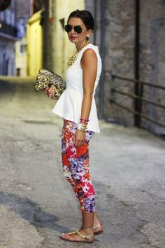 white peplum, floral pants, gold clutch, sandals, and necklace.